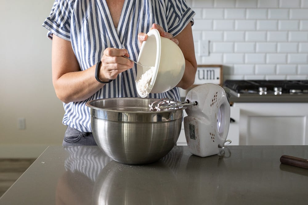 woman pouring flour mixture from small plastic white bowl into large stainless steel bowl
