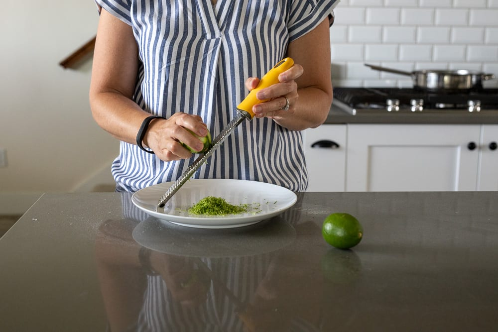 woman grating lime zest with a microplane onto a white dinner plate