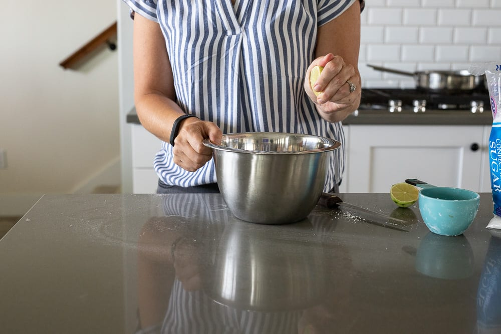 woman squeezing lime juice into stainless steel bowl