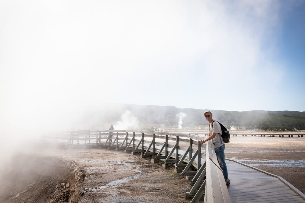 teenage boy standing by steaming midway geyser basin