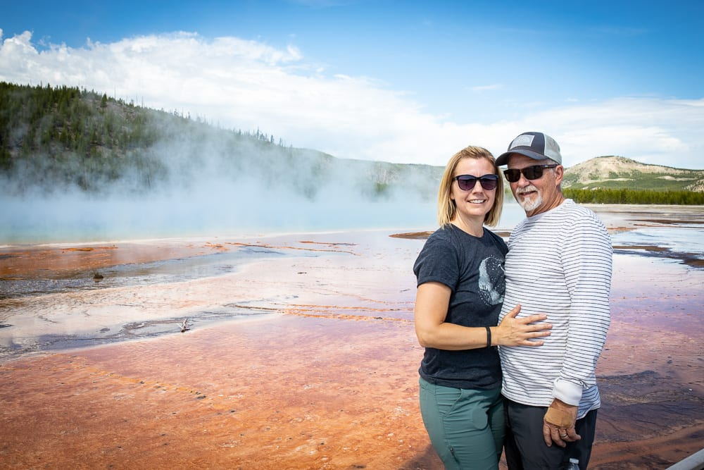 couple standing by hot springs in yellowstone national park.