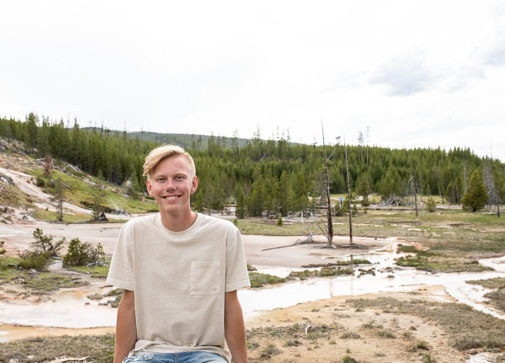 teenage boy sitting in front of hot springs in yellowstone national park