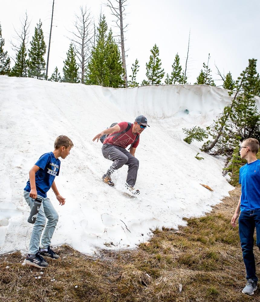 man sliding down snow on hiking trail