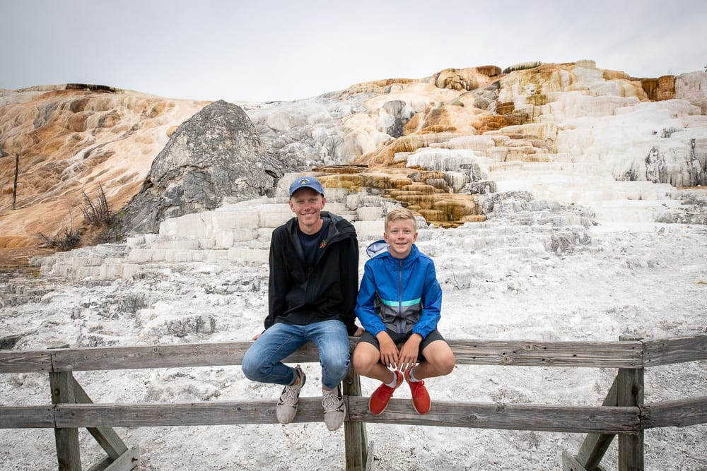 two boys next to basalt formations in yellowstone national park