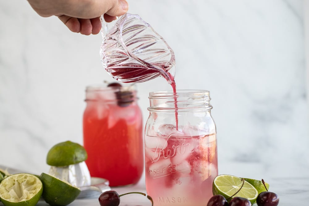 woman pouring cherry reduction from glass carafe into mason jar