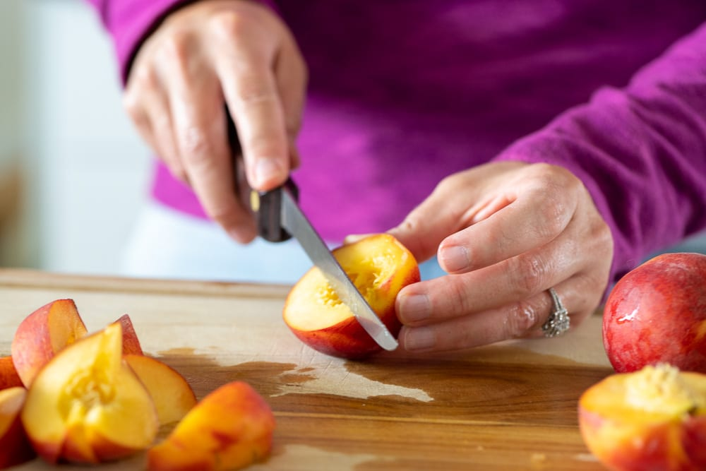 woman cutting peach wedges on wooden cutting board with knife