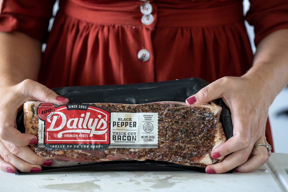 woman holding daily's black pepper thick cut bacon
