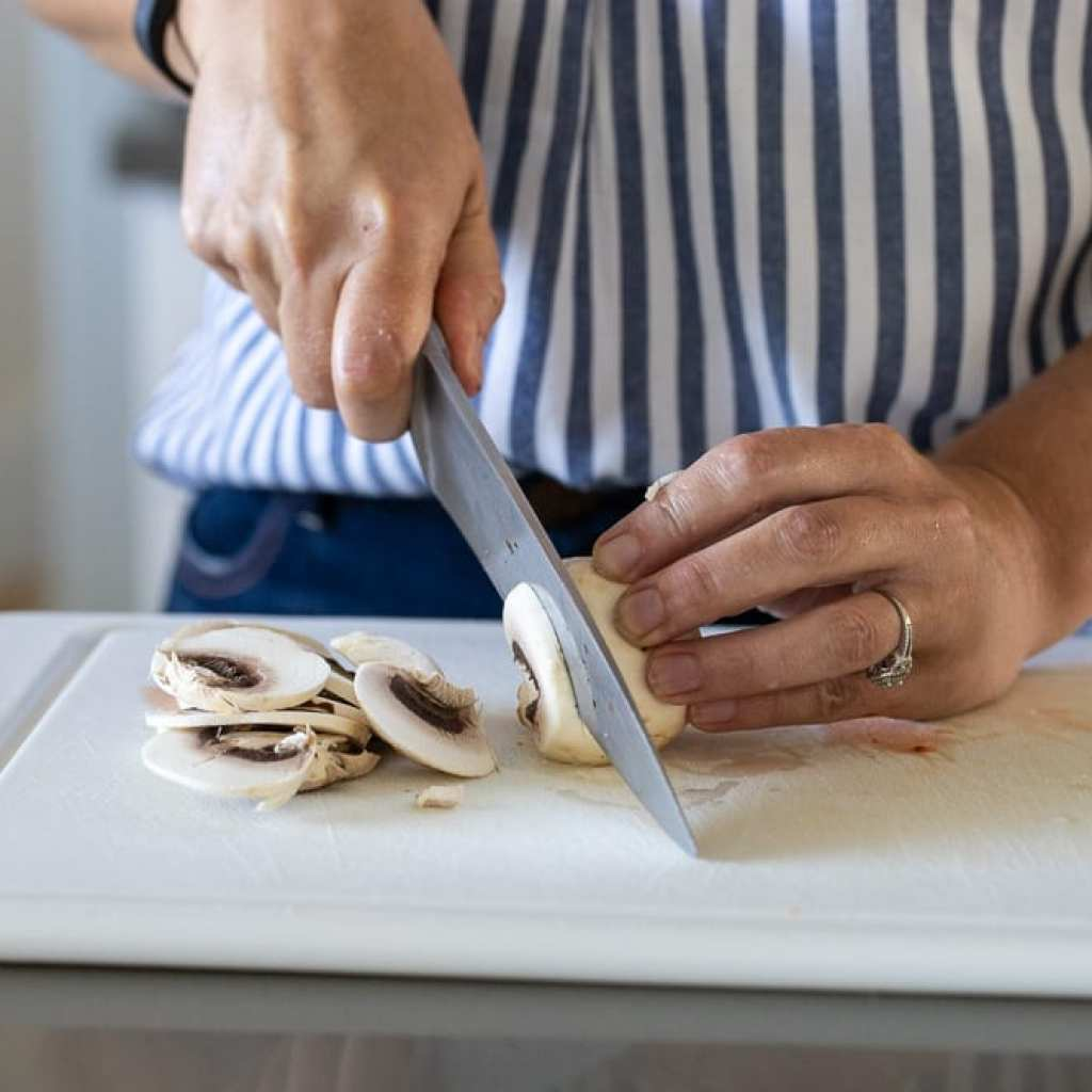 woman slicing with mushrooms with a chefs knife on a white cutting board