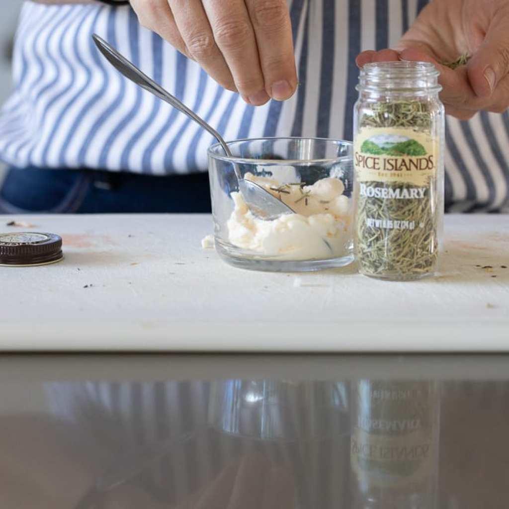 woman mixing rosemary into mayonnaise