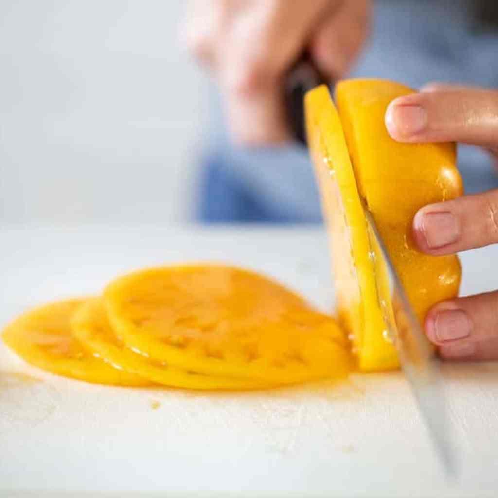 woman slicing heirloom tomatoes