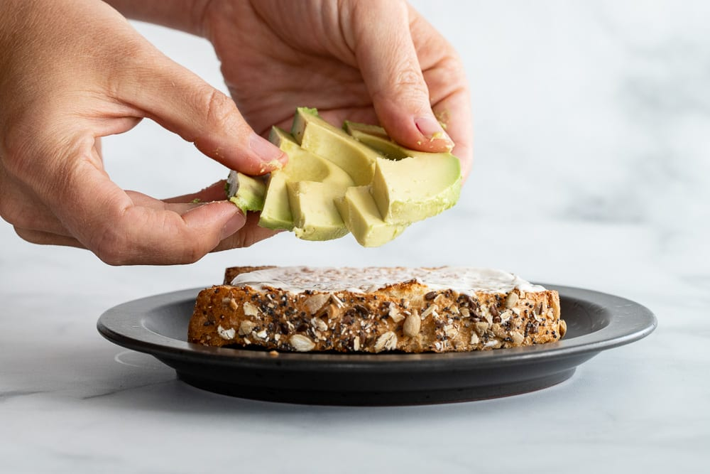 woman adding slice avocados to sandwich
