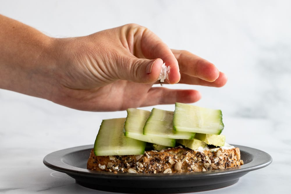 woman sprinkling salt on sliced cucumbers on sandwich