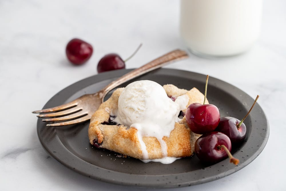 baked galette on black plate with cherries on it and a glass of milk in the background.
