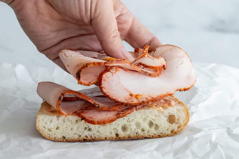 woman placing layers of boars head pepper turkey on sandwich