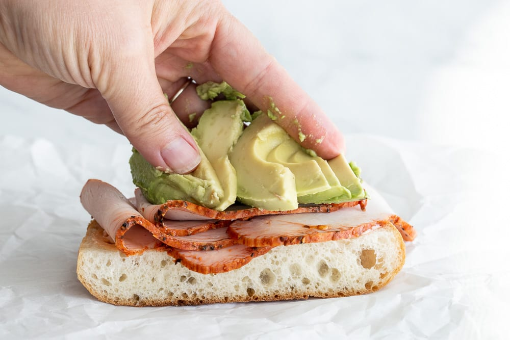 woman adding sliced avocados to sandwich
