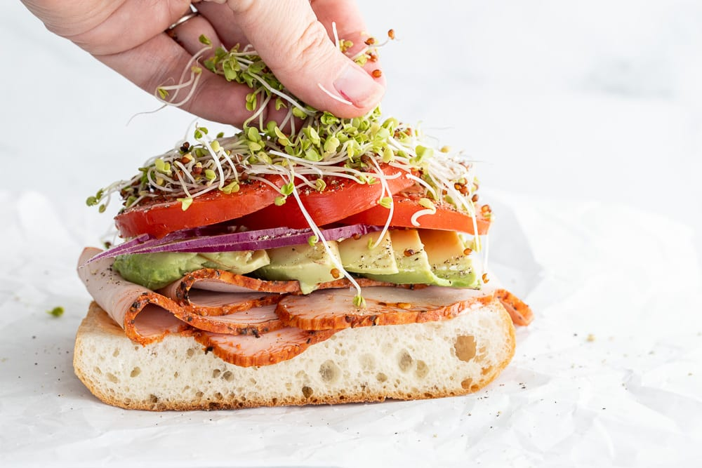 Woman adding sprouts to sandwich.