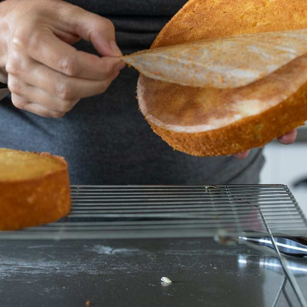 woman removing parchment paper from bottom of cake.