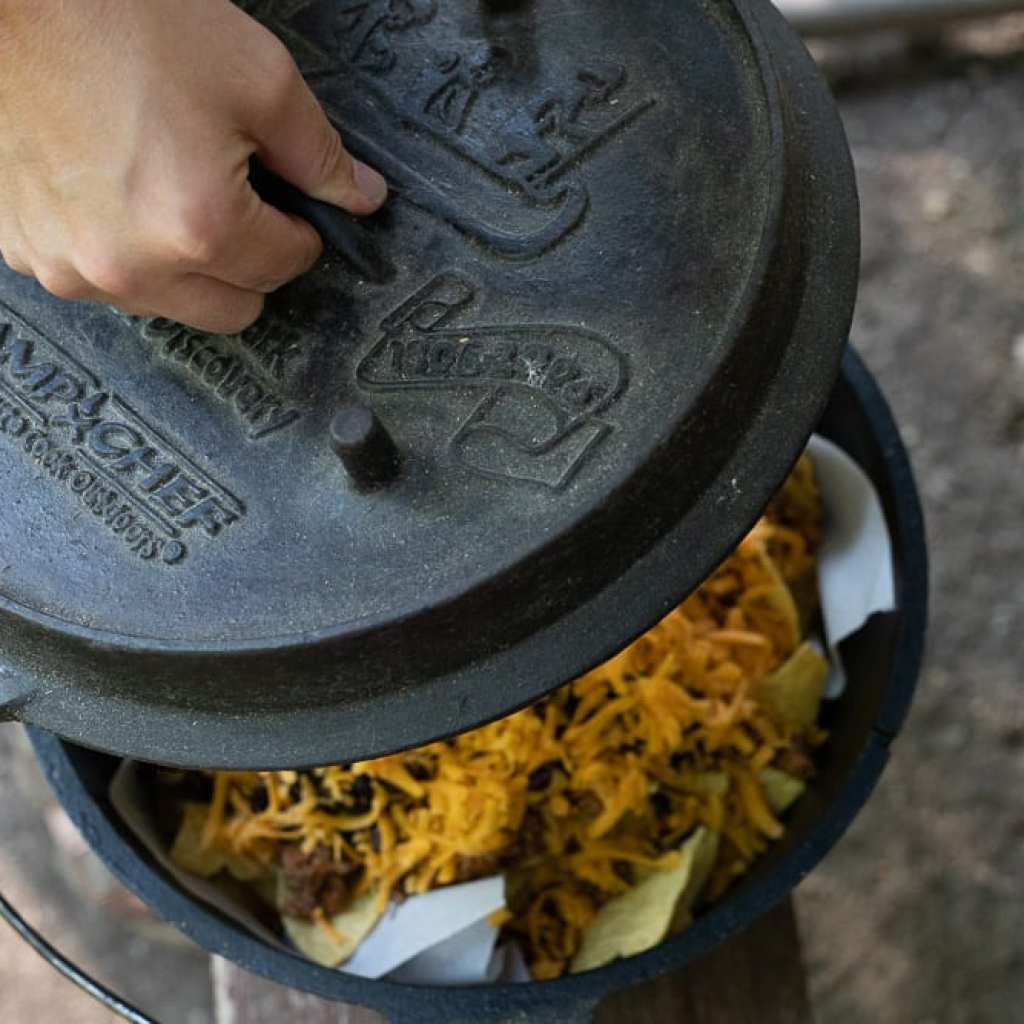 woman adding lid to dutch oven for cooking campfire nachos