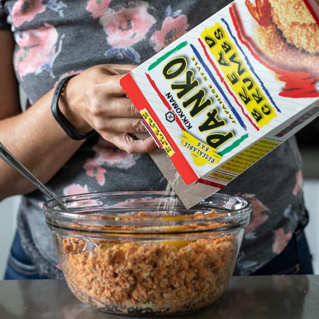 woman adding in panko to flaked salmon in a clear glass bowl
