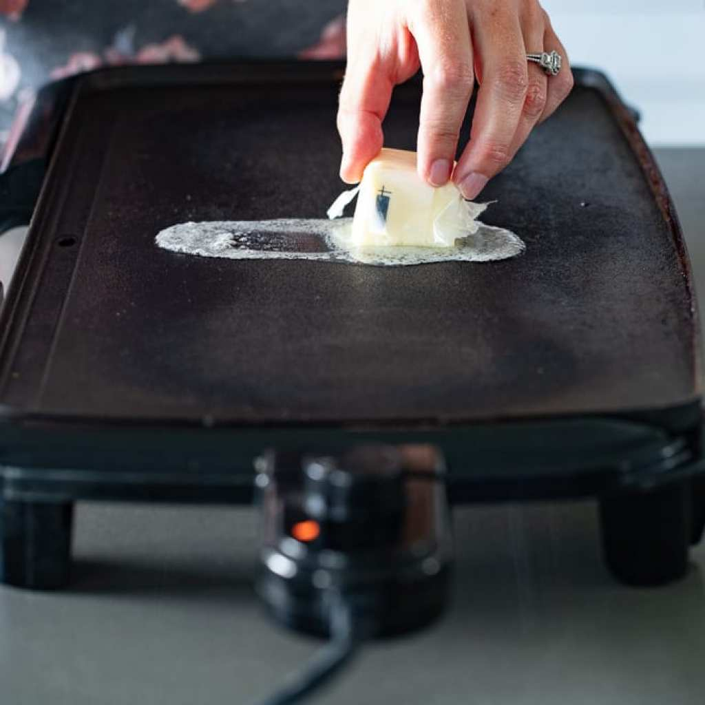 woman adding butter to heated electric griddle
