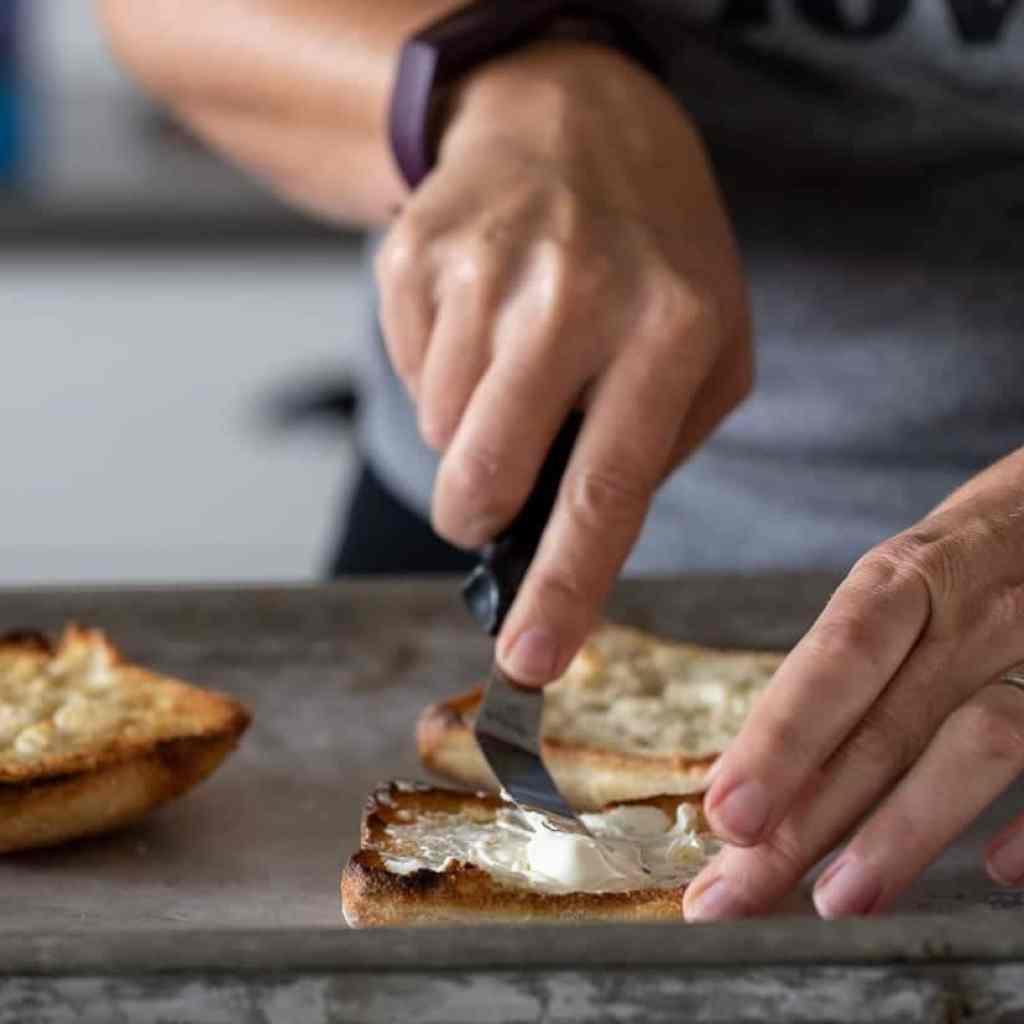 woman spreading cream cheese on a artisan bun