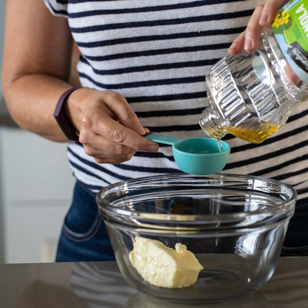 woman adding oil to glass bowl with softened butter