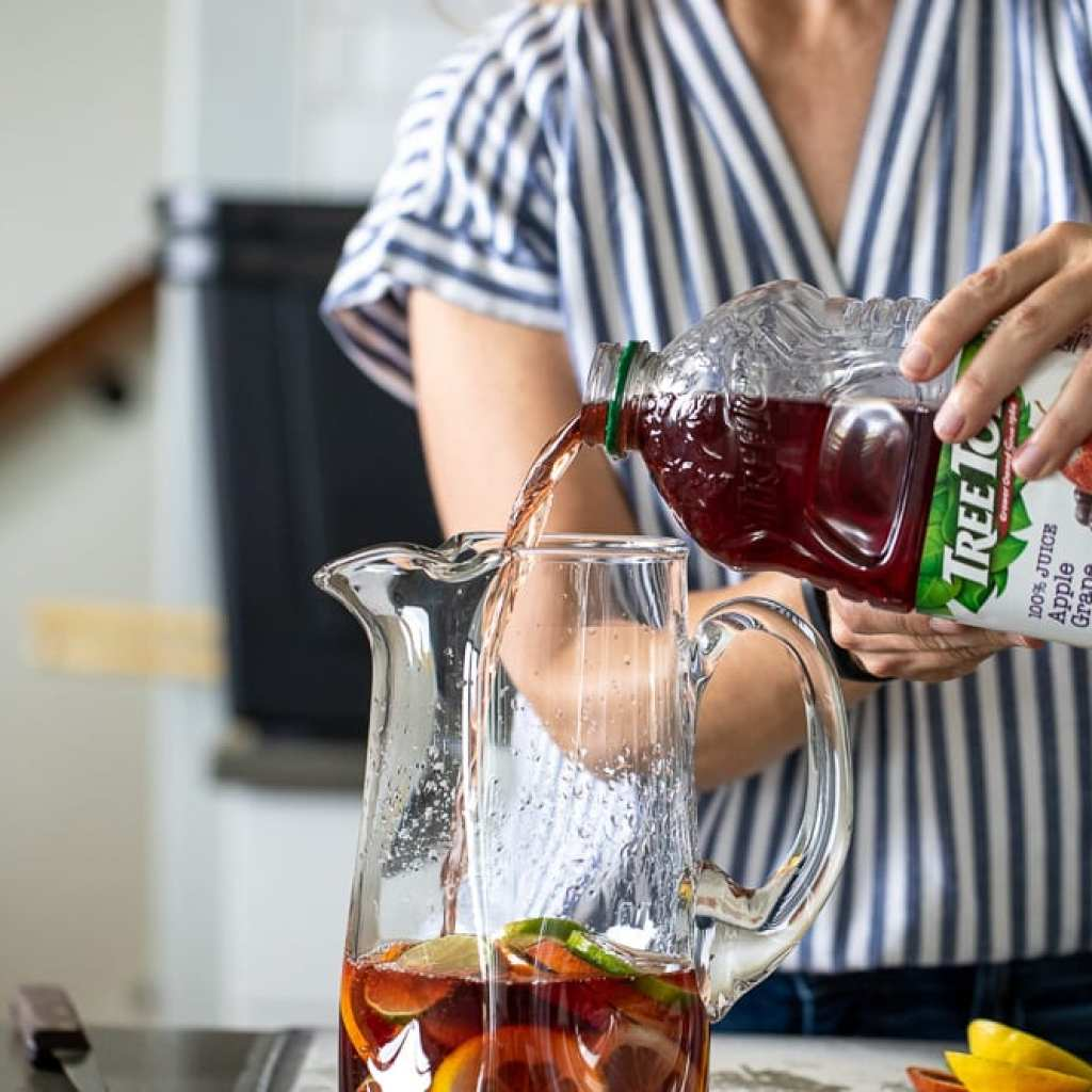 woman pouring Tree Top apple grape juice into glass pitcher