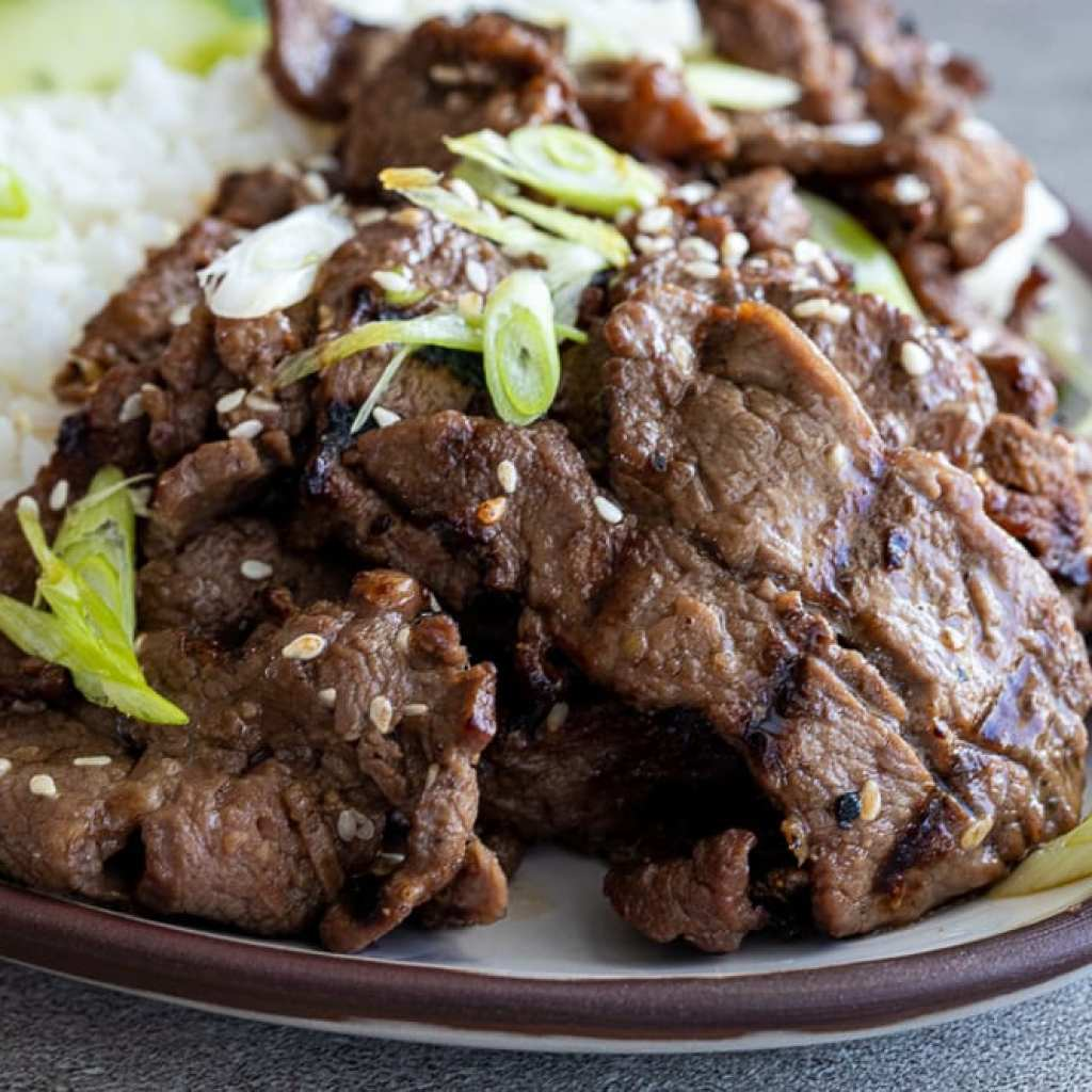 Tender and Flavorful Beef Bulgogi on ceramic platter with sliced green onions.