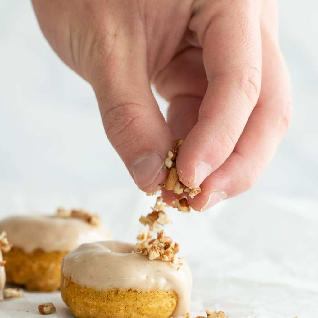 boy sprinkling chopped pecans over a pumpkin donut with maple glaze