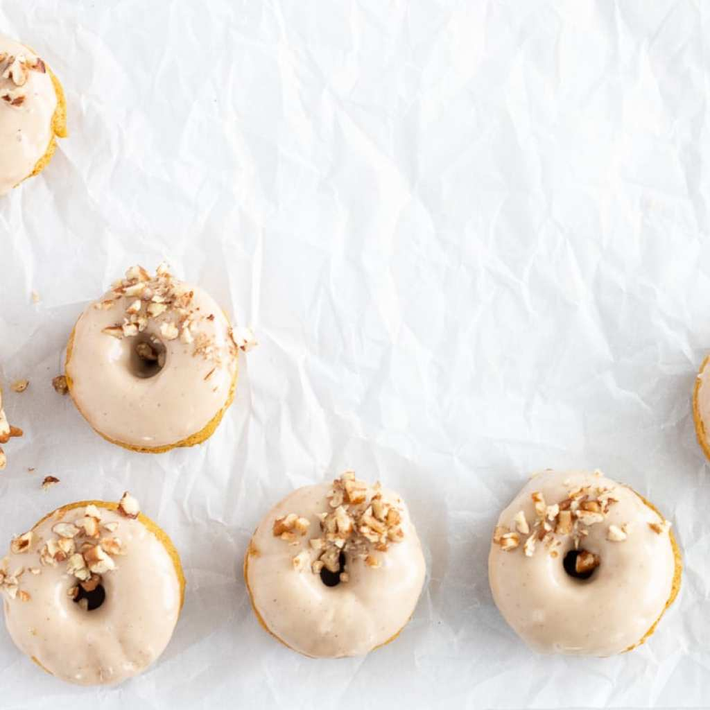 pumpkin donuts with maple glaze topped with chopped pecans