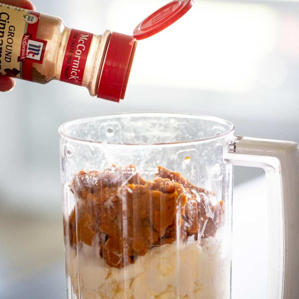woman adding cinnamon to blender with ice cream and pumpkin puree