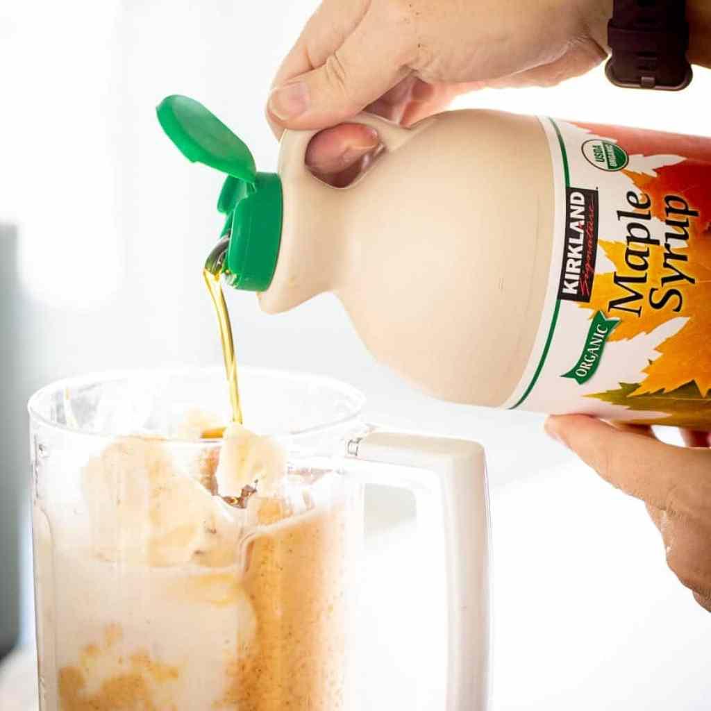 woman adding maple syrup to blend for pumpkin milkshake