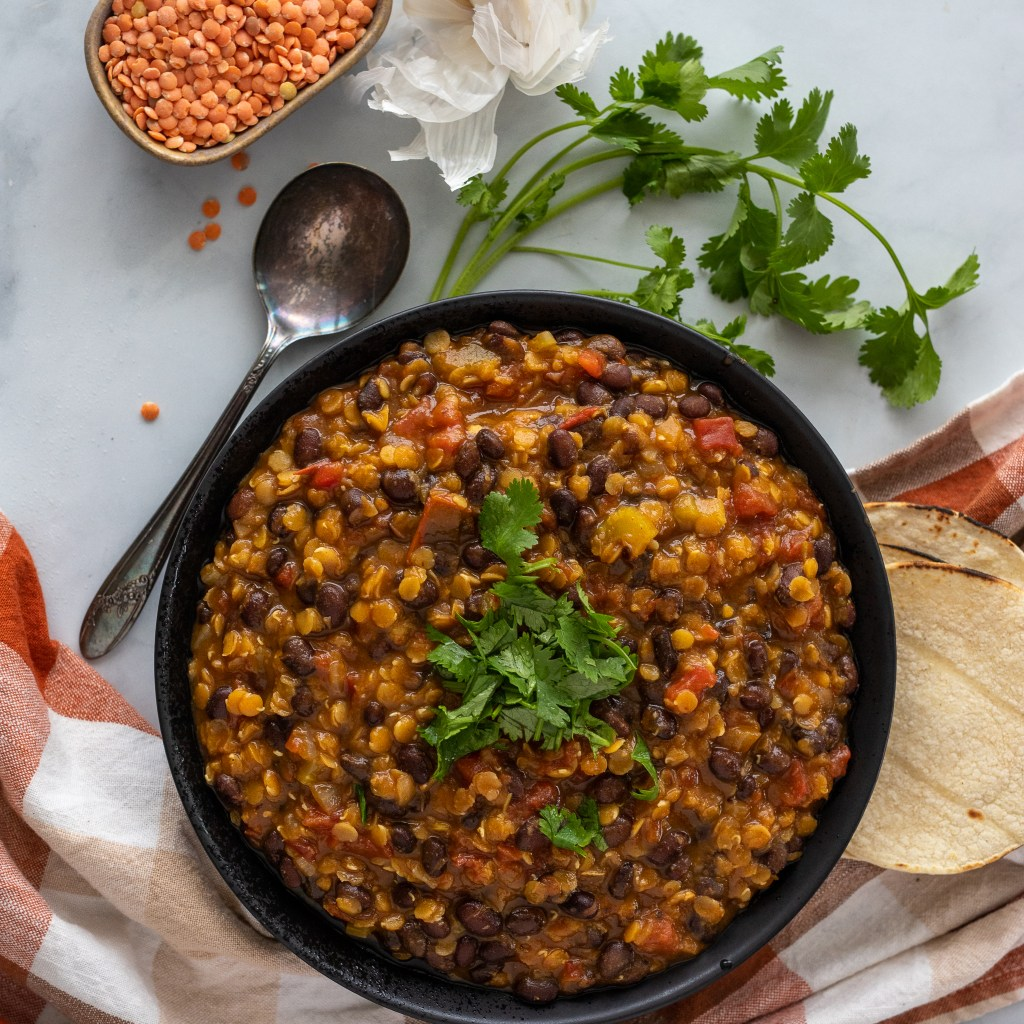Southwestern Vegetable Soup with Lentils in black bowl with cilantro and garlic on surface