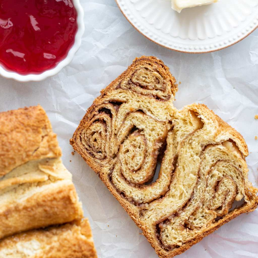 Povitica-Style Swirled Brioche sliced on parchment paper with butter and red currant preserves in background