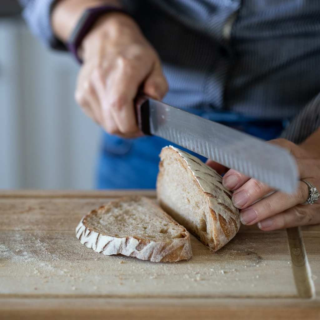 woman slicing whole wheat sourdough bread for toast