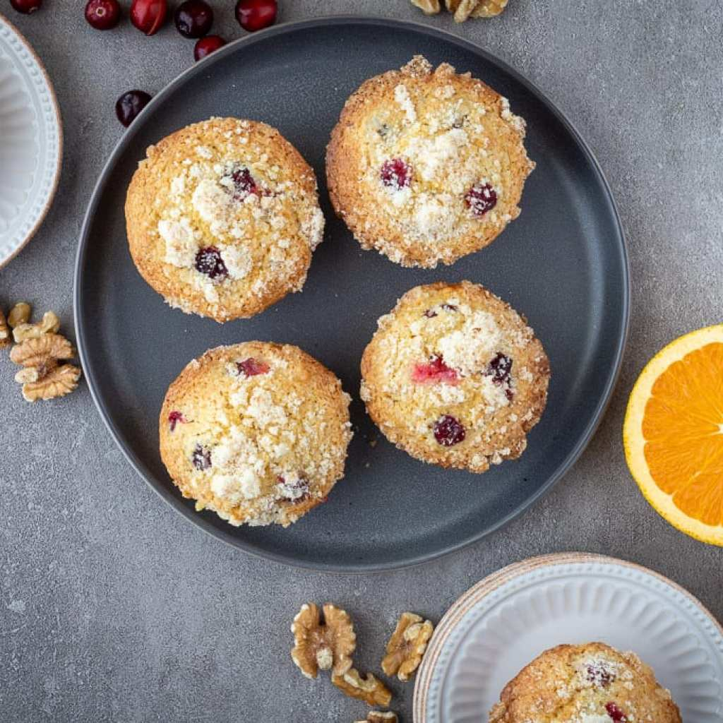 Fresh Cranberry Orange Muffins on gray plate with oranges, walnuts, and cranberries around it