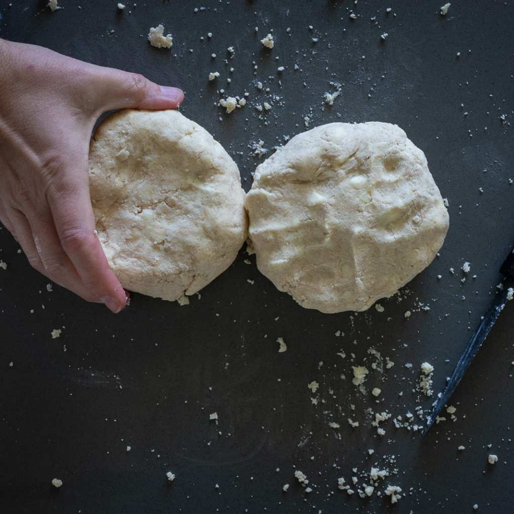 woman holding pie dough discs ready to be wrapped