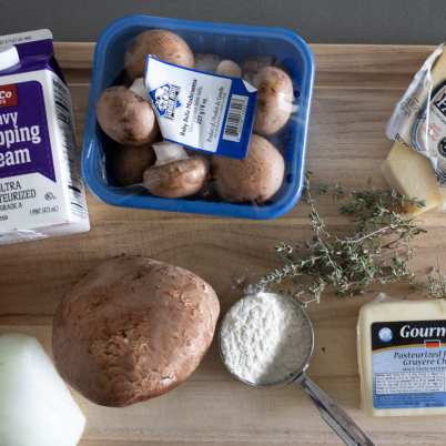 ingredients for wild rice bake on wood cutting board onions gruyere parmesan cheese mushrooms kale fresh thyme and heavy cream