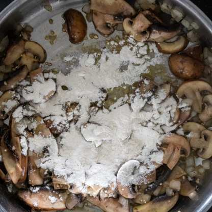 flour sprinkled on top of sauteed mushrooms and onions for making a roux
