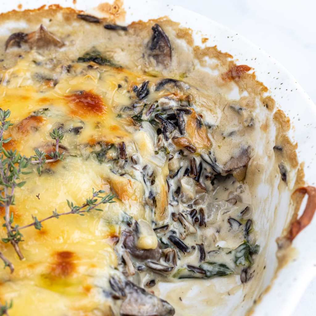 Baked creamy wild rice casserole with mushrooms in ceramic pie plate