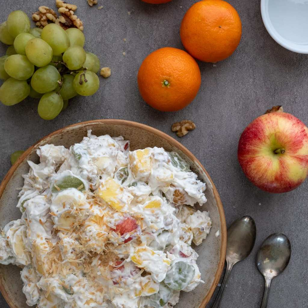 Easy And Healthy Ambrosia Salad on table with apple, oranges, grapes and walnuts