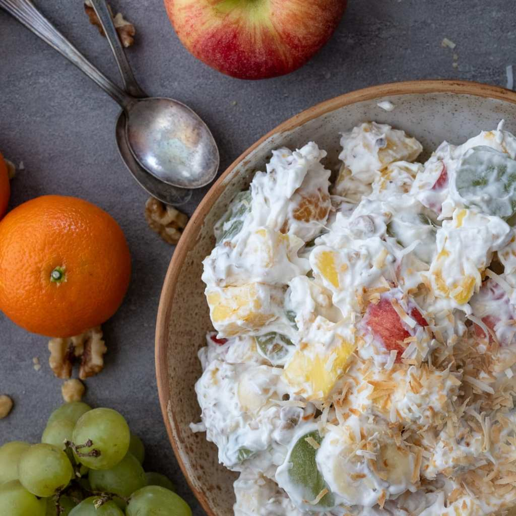 Easy And Healthy Ambrosia Salad in a ceramic bowl with oranges and walnuts on the table beside it.