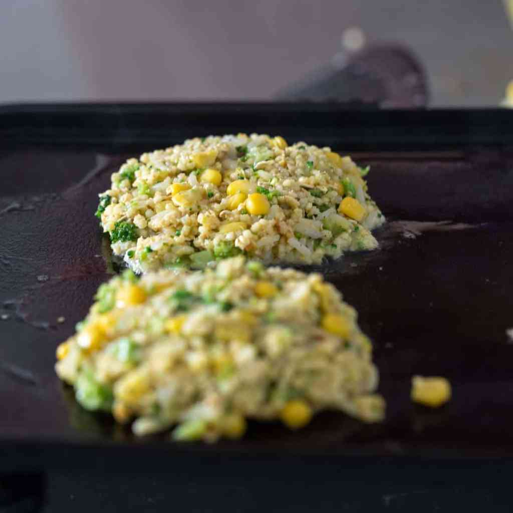 vegetable fritters cooking on griddle