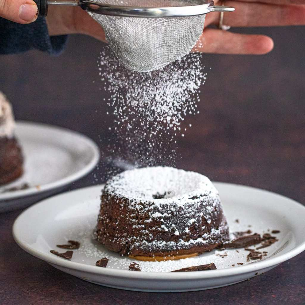 woman sprinkling powdered sugar over a lava cake