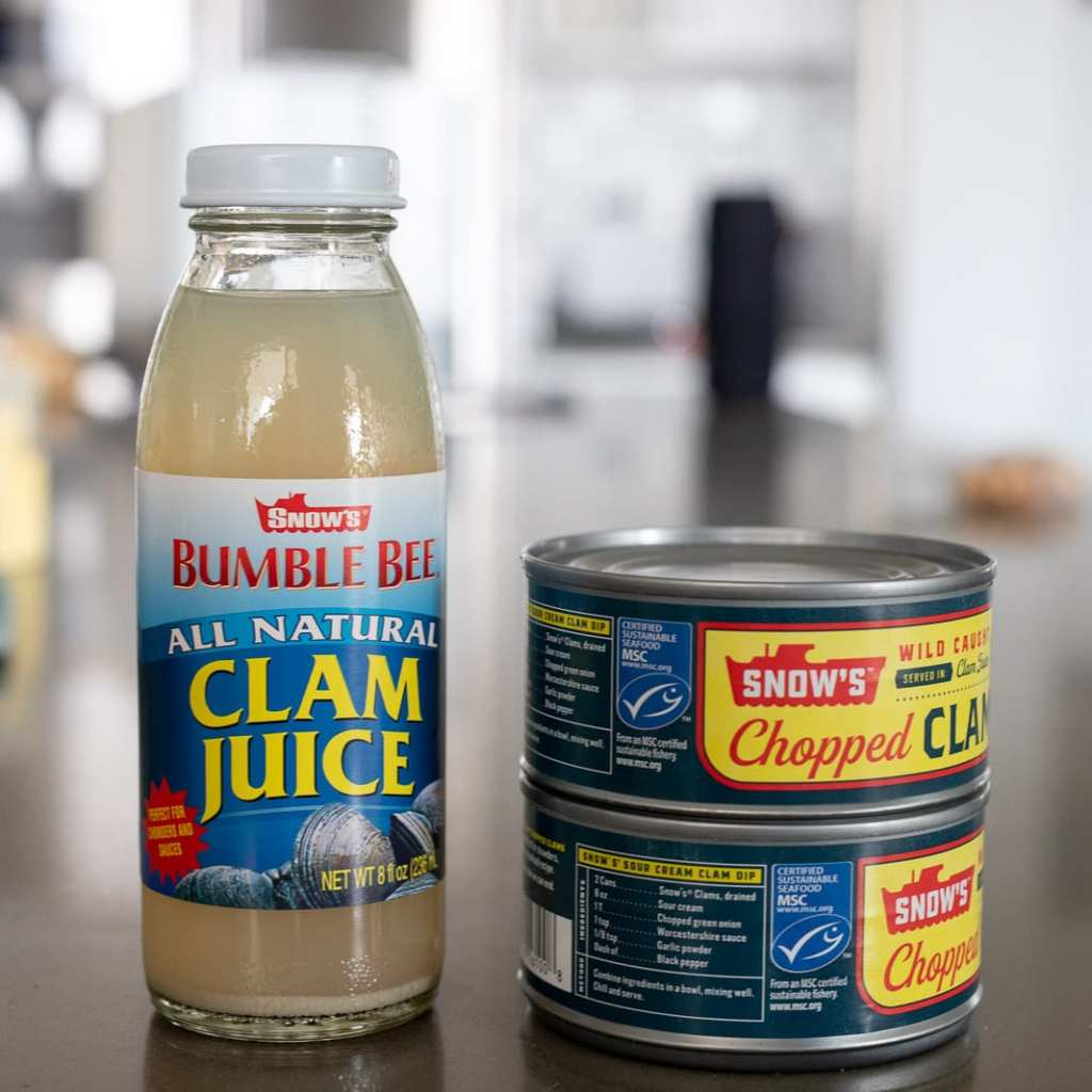 bumble bee clam juice and 2 cans of chopped clams on a counter top