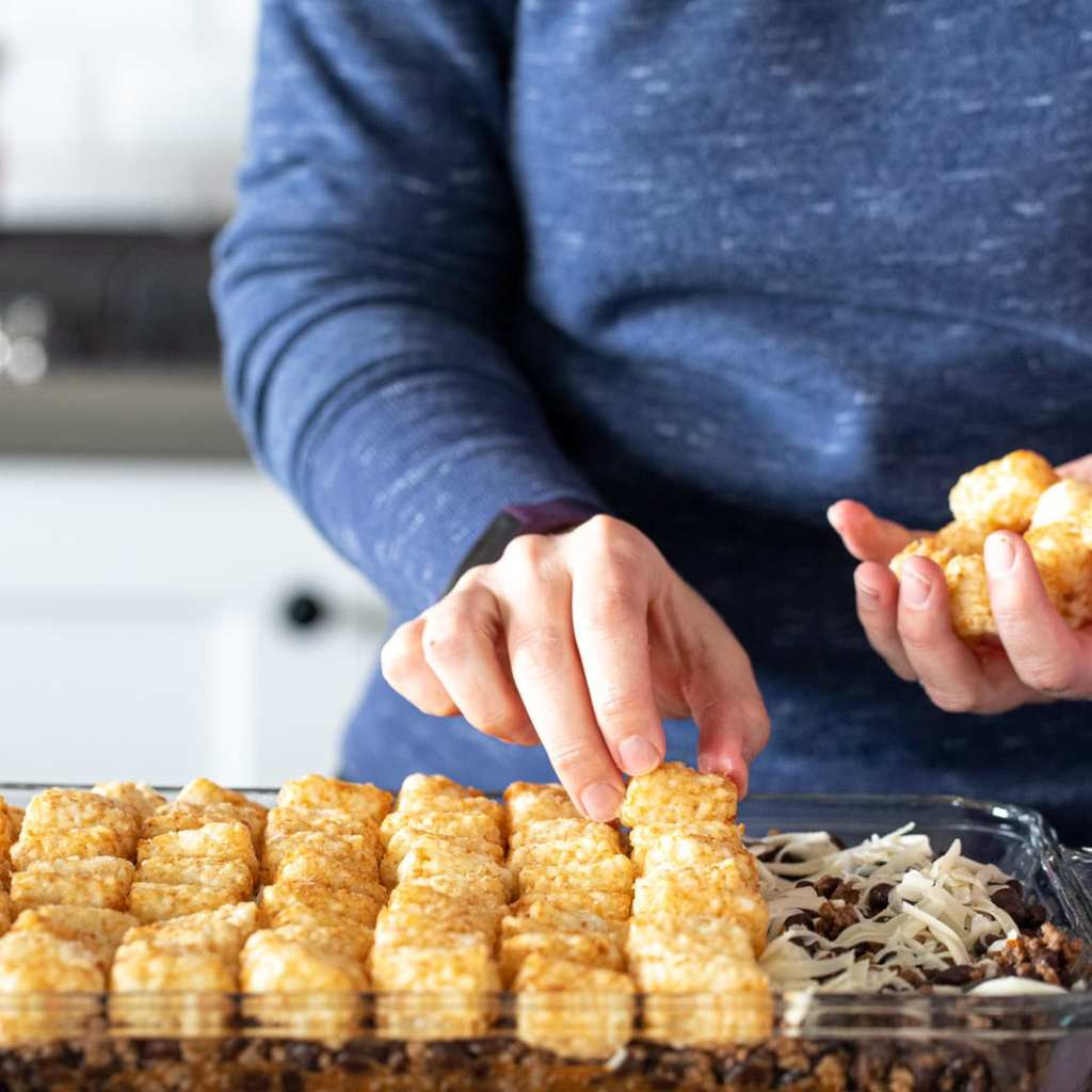 woman adding tater tots to the top of a casserole in a glass dish