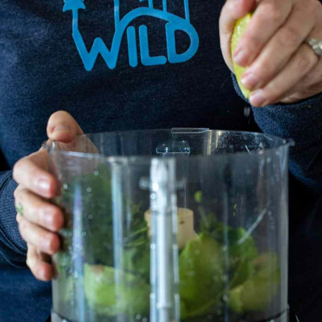 woman adding lime juice to a food processor with avocados and cilantro.