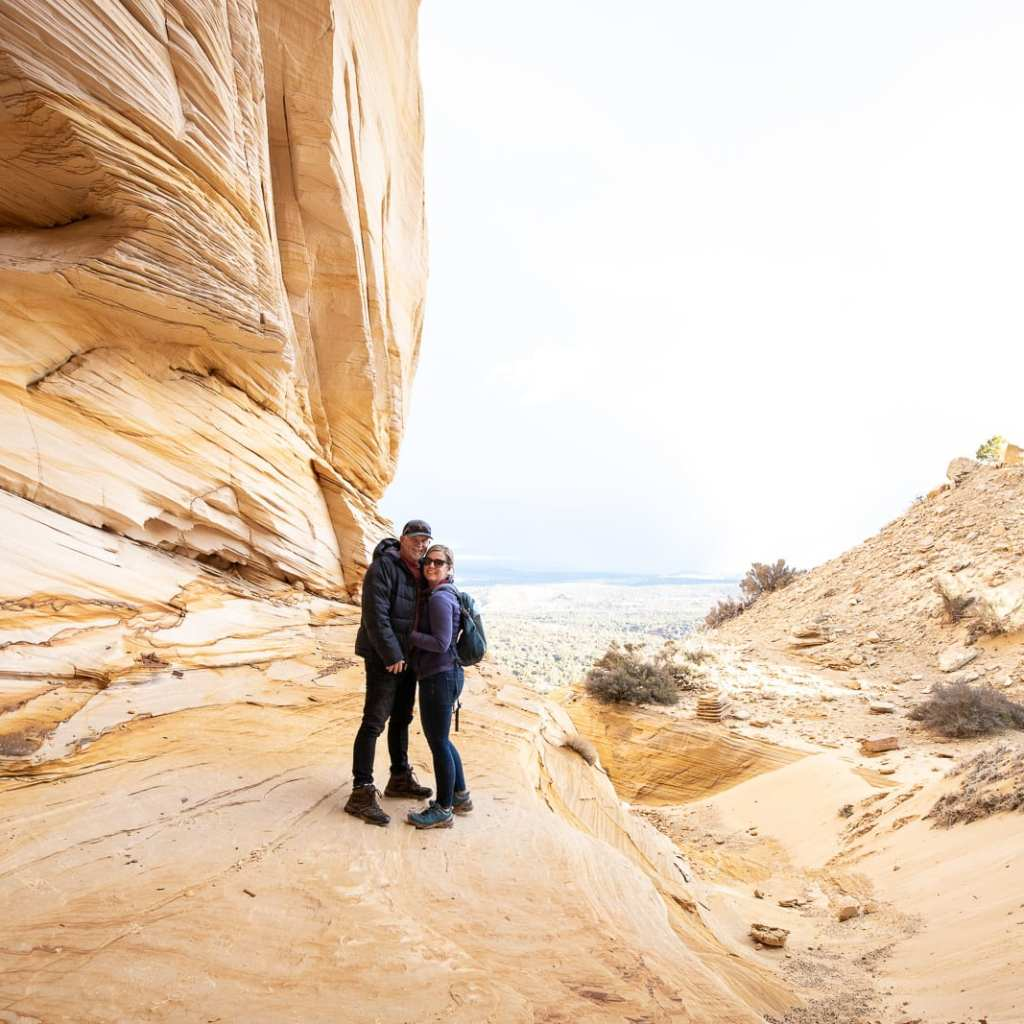 couple hugging at the mouth of the grand chamber utah