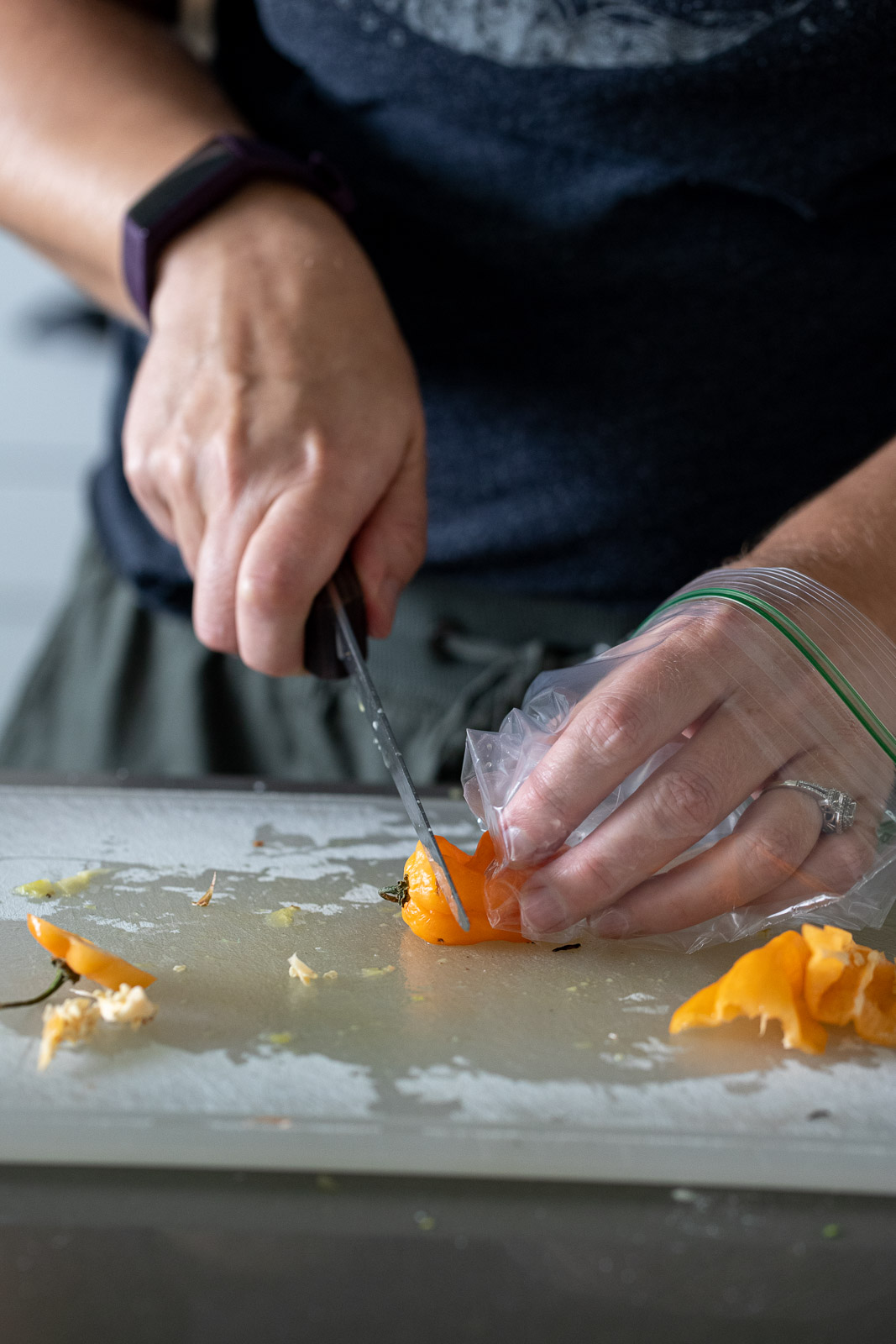 woman cutting up habanero peppers on a plastic cutting board.