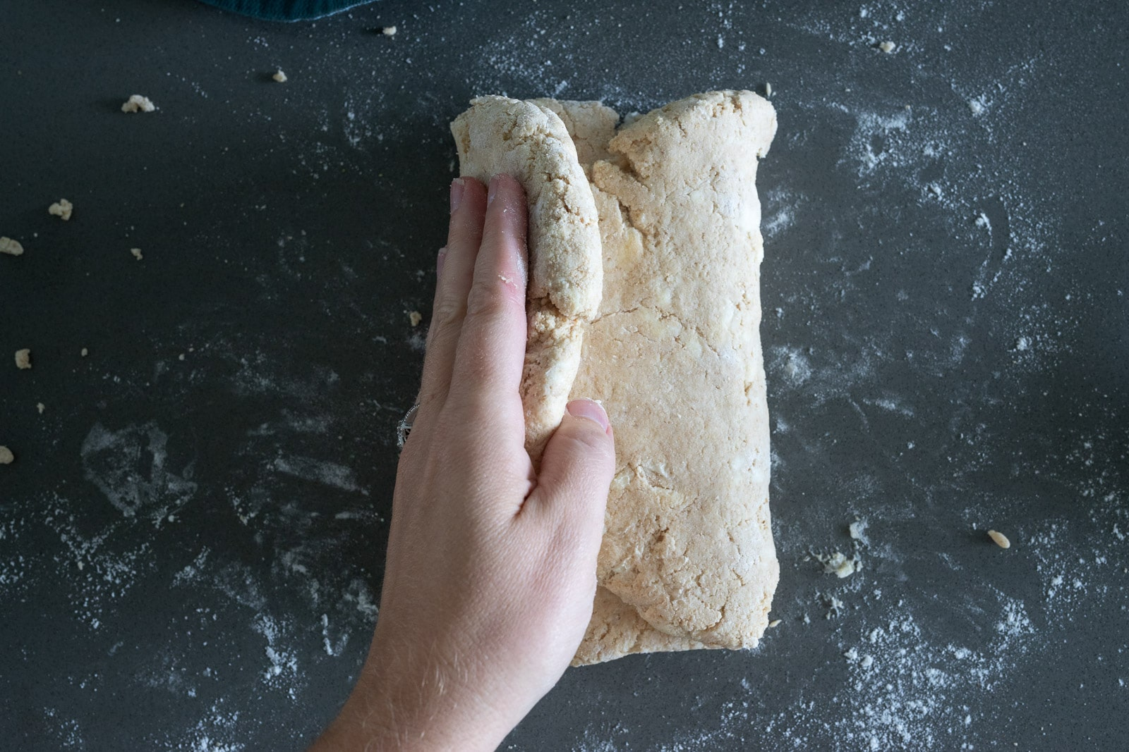 woman folding biscuit dough over to make biscuits.